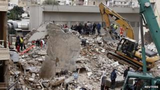 Workers remove rubble at the site of a collapsed building in Beirut, Lebanon, on 16 January 2012
