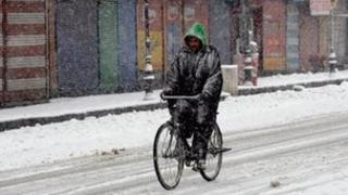 A cyclist in heavy snow in Srinagar in Indian Kashmir