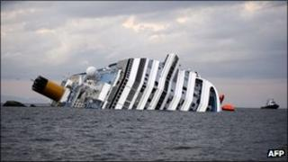 The Costa Concordia cruise ship lies on its side in the harbor of the Tuscan island of Giglio