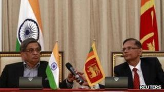 Sri Lanka's Foreign Minister Gamini Lakshman Peiris (R) passes a microphone to his Indian counterpart S.M. Krishna during their meeting in Colombo on 17 January, 2012.