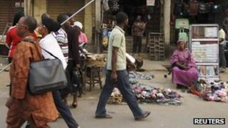People walk past market stalls after the suspension of a nationwide strike by labour unions, in Nigeria's commercial capital Lagos, 16 January 2012
