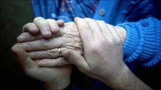 Carer holding elderly woman's hand