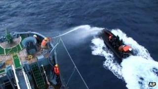Screen image from video provided by Japan's Institute of Cetacean Research showing a crew member on the Japanese whaling ship Yushin Maru No 2 spraying water cannon towards Sea Shepherd Conservation Society activists aboard a rubber boat in Antarctic waters on 18 January 2012