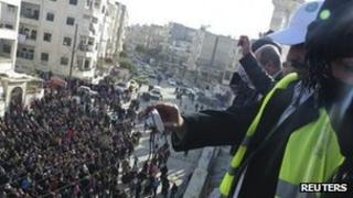 Arab League observers take photos of an anti-government march in the province of Idlib