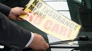 Sticker being put on uninsured car