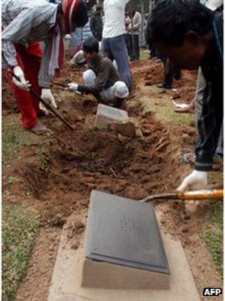Labourers dig at the grave of a World War II Japanese soldier buried at Guwahati war cemetery in Guwahati, northeast India on January 18 2012.