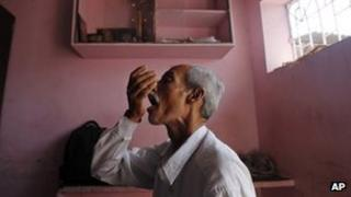 A tuberculosis patient takes medicines in India