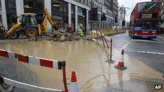A bus drives around flood water in Oxford Street