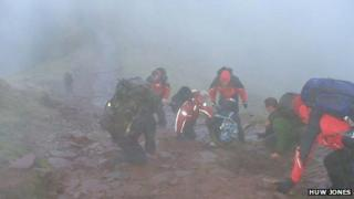 The Central Beacons mountain rescue team help the walkers down from Corn Du