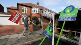"Man erecting ""for sale"" signs"