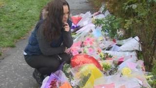 Darren Croxton's girlfriend lays flowers at the scene