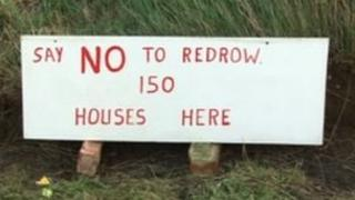 A sign opposing the houses in the ground