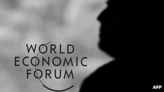 A guard stands next to a logo of the World Economic Forum