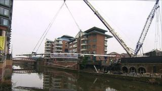 A crane lifts a bridge over the River Irwell into place