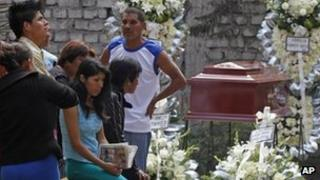 Relatives mourn one of the victims of the fire in Lima