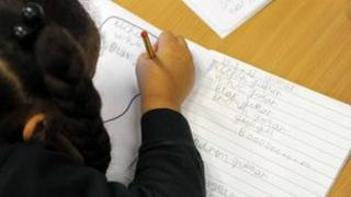 Primary school pupil writing in an exercise book