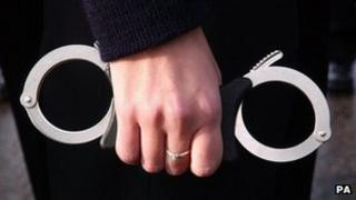 A policewoman holding handcuffs