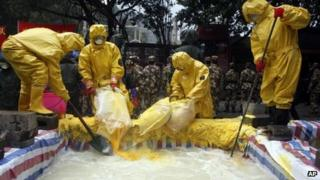 Policemen in chemical suits pouring neutralisers into water tainted by cadmium pollution in Nuomitan Reservoir in Liucheng county in China's Guangxi Zhuang Autonomous Region, on 30 January, 2012