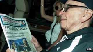 Rupert Murdoch holding a copy of the Times