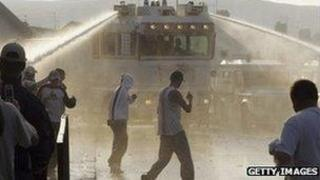 Water cannon being used on a group