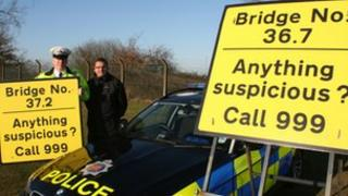 Two of the signs that have been hung on bridges on the A12