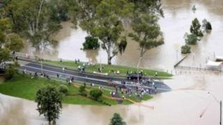 People gather on a road submerged by flood waters near the town of Moree, Queensland on 3 February, 2012