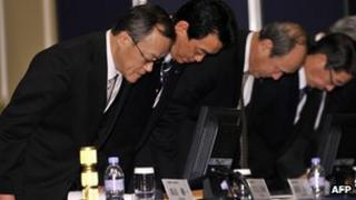 Olympus president Shuichi Takayama and company executives bow their heads