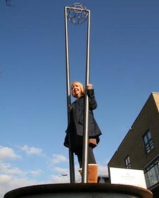 Liz Mannion underneath her sculpture.