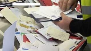 A Postman sorting mail