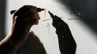 Teacher's hand writing on white-board
