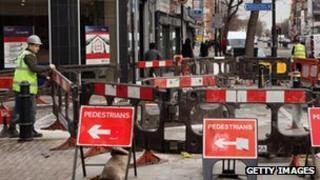 workmen digging up a pavement