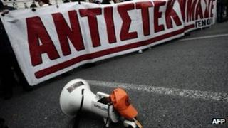 """A megaphone lies in the road in Athens beside protesters with a banner reading """"We resist"""", 9 February"""