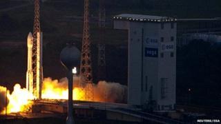 Vega rocket launching with bright smoke, next to buildings