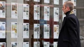 Man at estate agent window