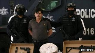 Mexican police present suspect Jaime Herrera along with captured drugs and guns