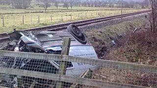 The van upside down and in a ditch after the collision with a train