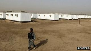 An Iraqi soldier stands guard in the former US military Camp Liberty outside Baghdad which will be the new temporary home for the People's Mujahideen Organisation of Iran (PMOI) exiles