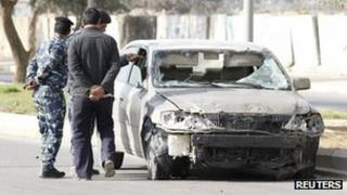 Police officers inspect a damaged vehicle at the site of a bomb attack in Baghdad, 19 February 2012