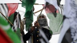 Activists of Pakistani Islamist groups and political parties hold their party flags during an anti-US protest rally in Islamabad on February 20, 2012