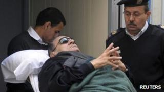 Former Egyptian president Hosni Mubarak lies on a gurney bed while leaving the Cairo courtroom where he is on trial