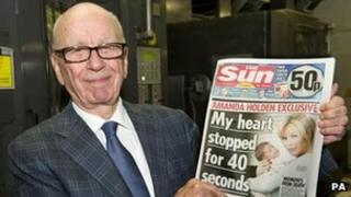 Rupert Murdoch holds the first edition of the Sun on Sunday newspaper