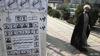 A cleric walks past election posters in Tehran (27 February 2012)