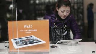 A customer tries out at an iPad at a retailer in Chongqing