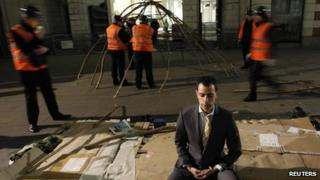 A protester meditating while bailiffs dismantle a tent