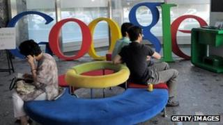 People sit on a sofa in front of a Google logo