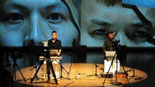 Multi-media artist Samson Young, left, during a performance of his work in Hong Kong last year
