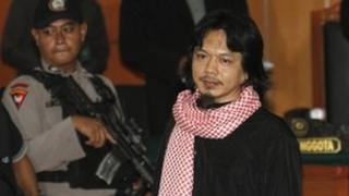Indonesian Islamic militant Pepi Fernando, right, leaves the courtroom after his trial at the West Jakarta District Court in Jakarta, Indonesia, Monday, March 5, 2012.
