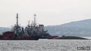 Two tugs alongside the nearly submerged ship