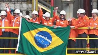 Brazilian President Dilma Rousseff joins workers to celebrate the construction of a new oil rig