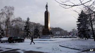 A man walks past a statue in Chisinau, Moldova (March 6, 2012)
